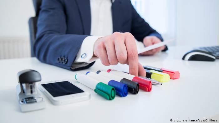 Мужчина в деловом костюме раскладывает разноцветные маркеры на столе в бюро
