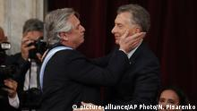 In this Dec. 10, 2019 photo, Argentina's new President Alberto Fernandez, left, embraces outgoing president Mauricio Macri after taking the oath of office at the Congress in Buenos Aires, Argentina. (AP Photo/Natacha Pisarenko)  