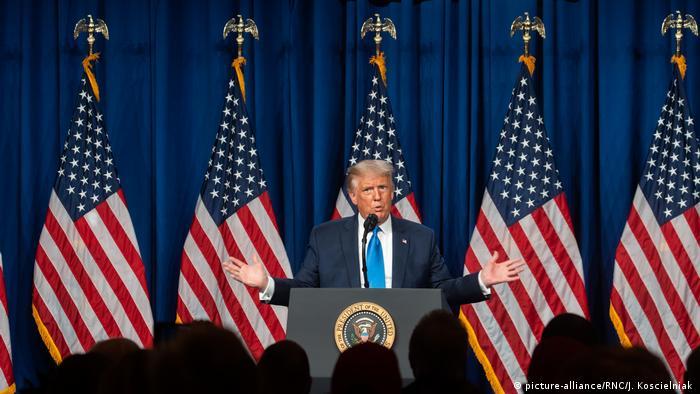 Donald Trump discursa em púlpito, com bandeiras americanas ao fundo