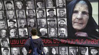 A boy pauses in front of a wall-sized poster depicting the faces of 90 survivors of the mass killings of Armenians in the Ottoman Empire