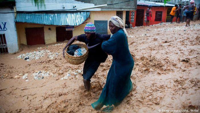 People selling from the market walk in the flooded street in the neighborhood of Pétion ville, Haiti