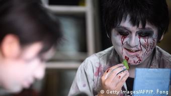 Kenta Wiana (ka.) memoles wajahnya agar tampak seperti zombi