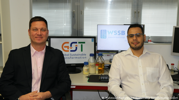 A picture of Thomas Brück and Mahmoud Masri in front of a computer screen flashing their company's logo