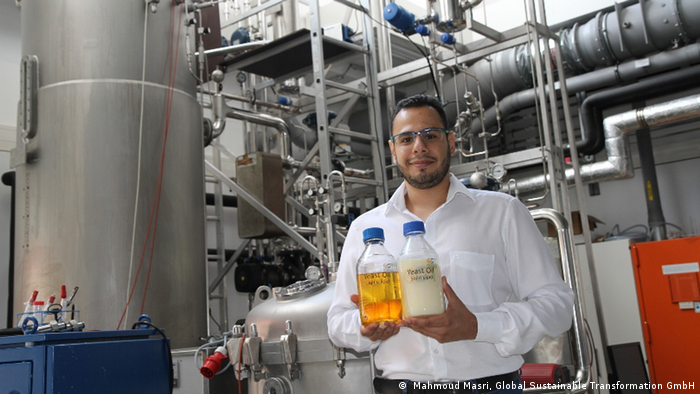 Mahmoud Masri standing next to a bioreactor and holding two bottles of oils made from yeast