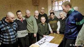 Заключенные изучают листовку кандидата в депутаты