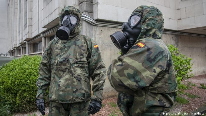 Spanish army soldiers wait to have their uniform disinfected