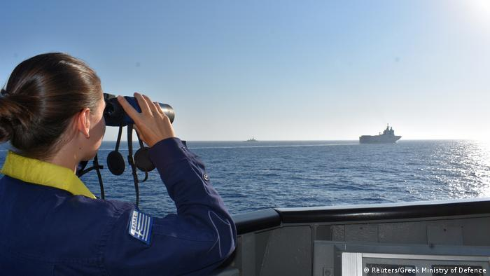 A woman looks through binoculars as Greek and French vessels maneuver during a military exercise in the Mediterranean Sea