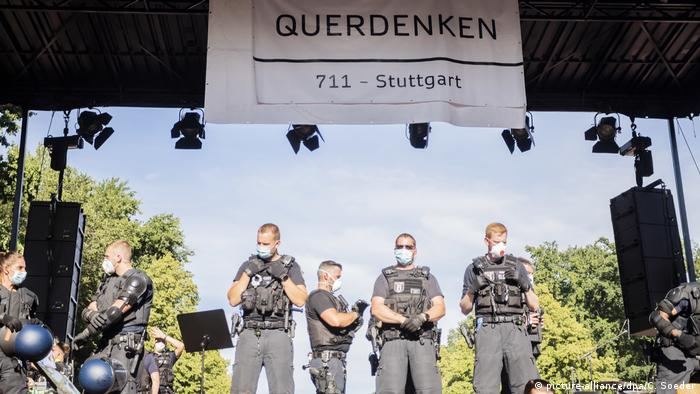 Polizisten auf einer Bühne, darüber ein Plakat Querdenken 711 Stuttgart) (picture-alliance/dpa/C. Soeder)