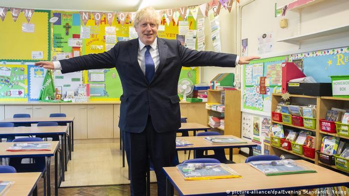 Boris Johnson abre los brazos en un salón de clase