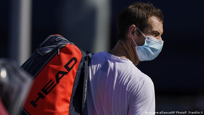 Tenista Andy Murray de máscara protetora e mochila