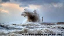 A massive wave dwarfs a lighthouse during a ocean storm