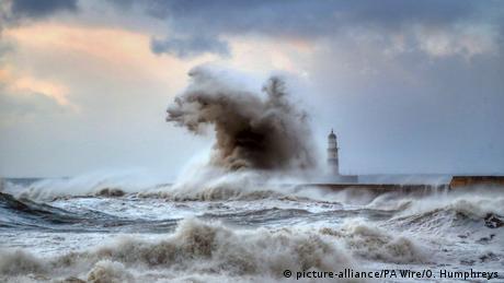 A massive wave dwarfs a lighthouse during a ocean storm
