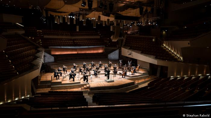 Musicians positioned on the semicircular stage of the otherwise completely empty Berlin Philharmonie