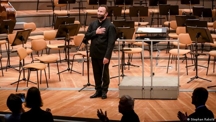 Kirill Petrenko alone onstage, hand on heart in a gesture of gratitude to applauding concert visitors