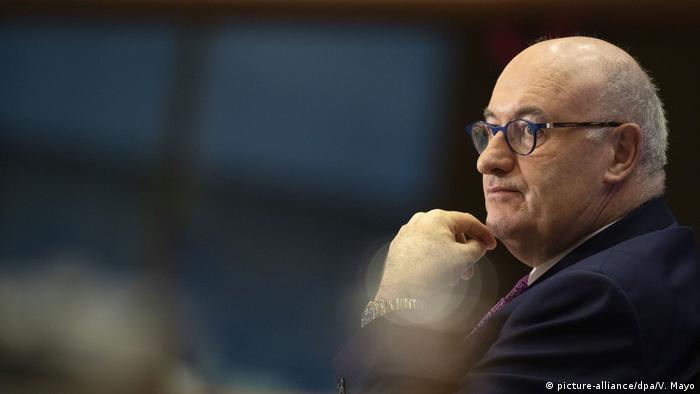 Homem de óculos, paletó e gravata, olhando para a esquerda