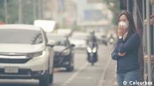 Thailand Frau mit Atemschutzmaske steht im Smog am Strassenrand in Bangkok