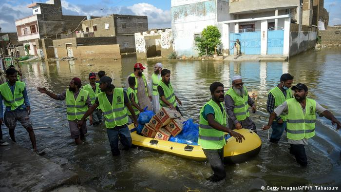 Volunteers distribute food to flood-affected residents at a flooded area after heavy monsoon rains in Pakistan's port city of Karachi on August 26, 2020