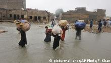 Local residents carry salvaged belongings as they wade through a flooded area during a heavy monsoon rains in Yar Mohammad village near Karachi, Pakistan, Thursday, Aug. 27, 2020. Pakistan's military said it will deploy rescue helicopters to Karachi to transport some 200 families to safety after canal waters flooded the city amid monsoon rains. (AP Photo/Fareed Khan) |