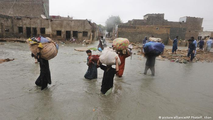 Residents carry belongings as they wade through a flooded area during a heavy monsoon rains in Karachi in August 2020