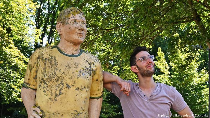 اللاجئ السوري محمد تحسين بيك بجانب تمثال يرمز للاعب كرة قدم في مدينة كايزرسلاوترن 20.08.2020