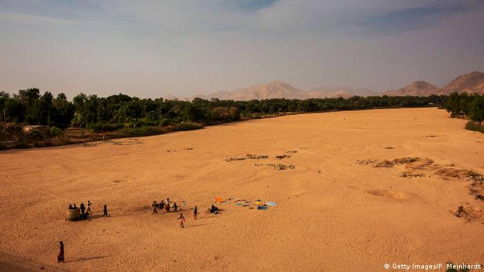 People stand in the sandy bed of an empty river