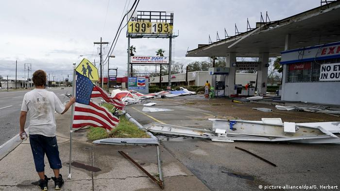 A man holds an American flag in a street surrounded by debris