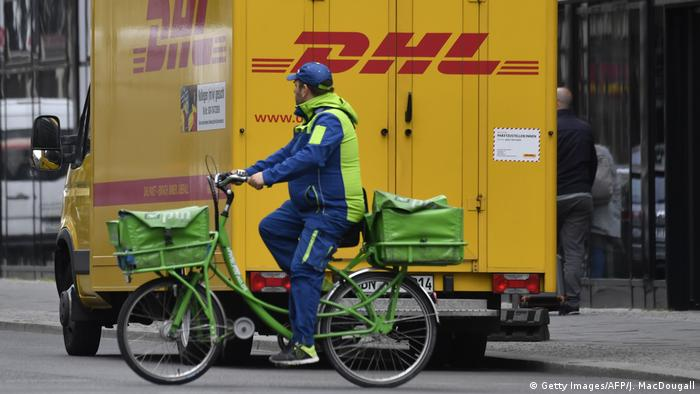 A postman of the Pin AG mail delivery company cycles past a delivery truck of DHL on May 15, 2019 in Berlin.