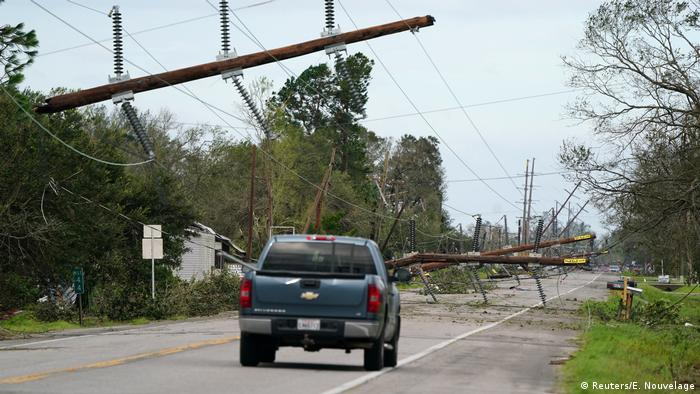 A car drives down a street with downed power lines