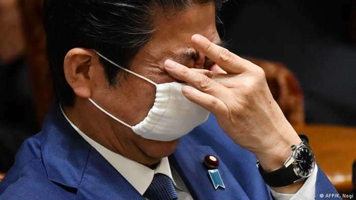 Japan's Prime Minister Shinzo Abe adjusts his face mask during an upper house budget committee session at the parliament in Tokyo on April 30, 2020