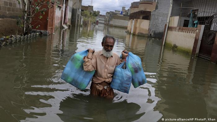 A man wades through a flooded street in Karachi after heavy monsoon rains
