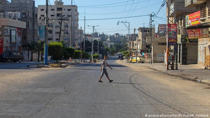 Ein junger mann geht über eine leere Straße (picture-alliance/Pacific Press/R. Habboub)