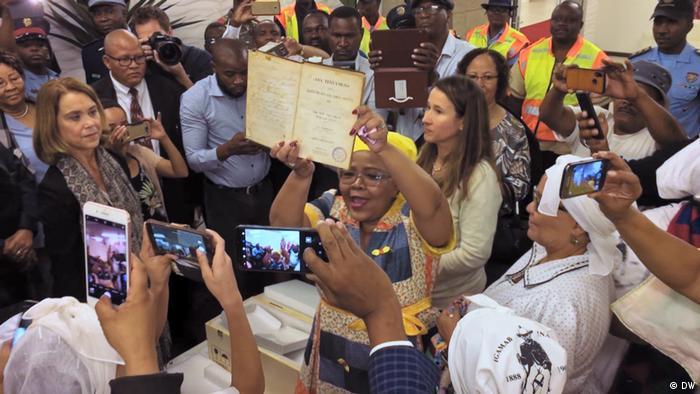 Die Witbooi-Bibel wird bei ihrer Ankunft am Flughafen in Windhoek in Namibia von einer Menschenmenge gefeiert (Bild: DW)