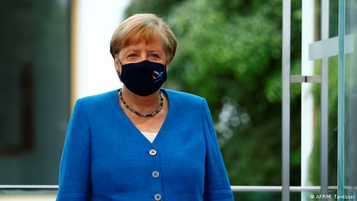 German Chancellor Angela Merkel wears a black face mask ahead of a press conference