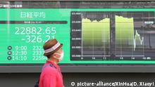 28.08.2020, Japan, Tokio: Ein Passant trägt einen Mundschutz und geht an einer elektronischen Anzeigetafel vorbei, die den Aktienindex Nikkei 225 zeigt. Der Markt in Tokio schloss mit Verlusten, da die Stimmung der Anleger durch Berichte getrübt wurde, wonach der japanische Ministerpräsident Abe aufgrund von Gesundheitsproblemen von seinem Amt zurücktreten wird. Foto: Du Xiaoyi/XinHua/dpa +++ dpa-Bildfunk +++ |