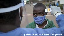 A Burundian refugee from Mahama camp in Rwanda is checked for fever as a precaution against the spread of the coronavirus after arriving back in Gasenyi, Burundi, Thursday, Aug. 27, 2020. Nearly 500 Burundian refugees living in Rwanda began their journey back to their home country Thursday, the first group to return from Rwanda after five years in exile following deadly political violence that sent many fleeing. (AP Photo/Berthier Mugiraneza)  