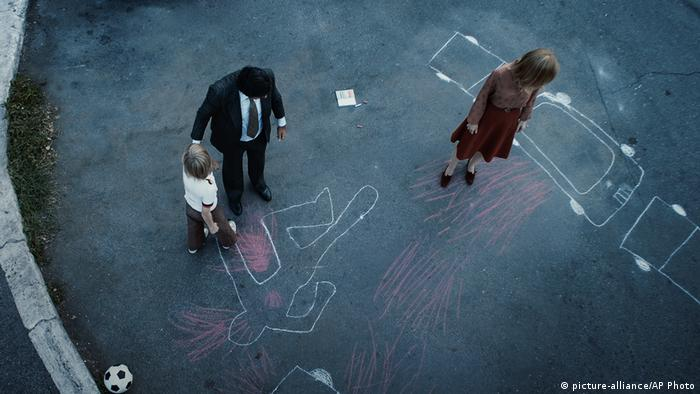 Film still from Padrenostro showing parents and a kid from a bird's-eye view with drawings in chalk on a concrete courtyard (picture-alliance/AP Photo)