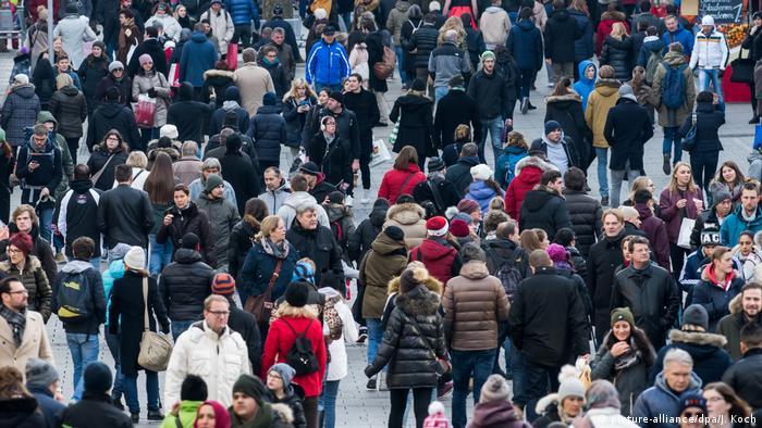 Centenas de pessoas caminham por rua em Munique
