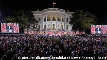 Donald Trump auf einer Bühne vor einer großen Menschenmenge, hinter ihm das Weiße Haus (picture-alliance/Consolidated News Photos/E. Scott)
