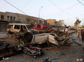 Afghans inspect the damage after a car bomb