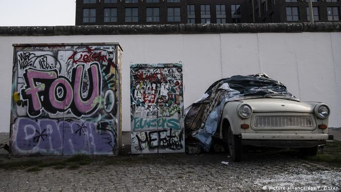 Duas caixas cheias de grafite ao lado de um carro antigo diante de um muro branco