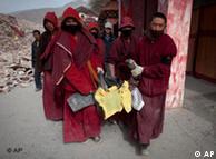 几名僧人抬走一位死者尸体