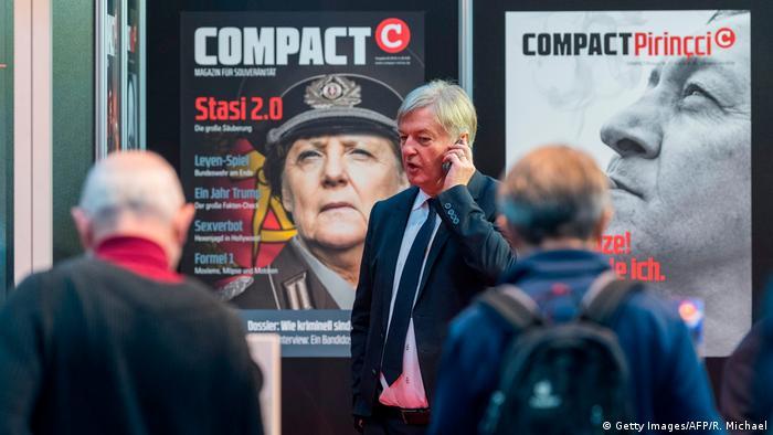 Jürgen Elsässer making a phone call, standing infront of posters vilifying chancellor Merkel