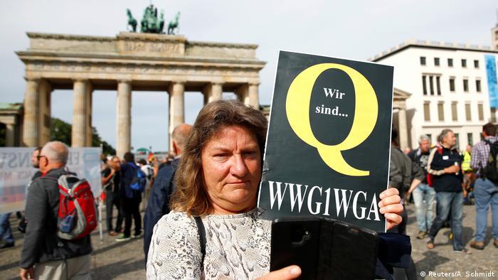 Mulher exibe símbolo da teoria QAnon durante protesto contra as medidas anticoronavírus em Berlim