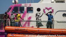 White boat hull, partly painted pink, with a Banksy portrait of a giarl and four men on board wearing facial coverings