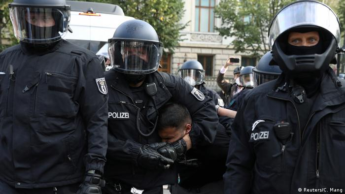 Police officer restrains a protester in Berlin