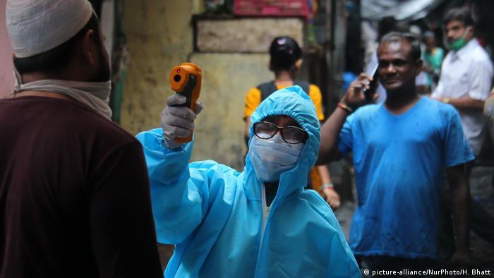 Pessoa com roupa de proteção mede febre à distância em outra pessoa