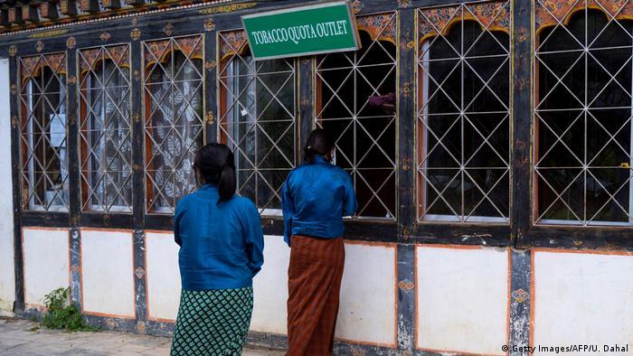 Zwei Frauen stehen vor einem geschlossenen Fenster, darüber ein Schild, das auf den Tabakverkauf hinweist Getty Images/AFP/U. Dahal)