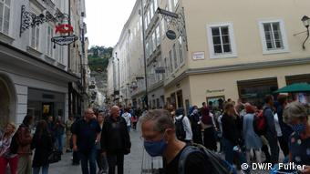 Crowds in a narrow Salzburg street, one man wearing a facial covering
