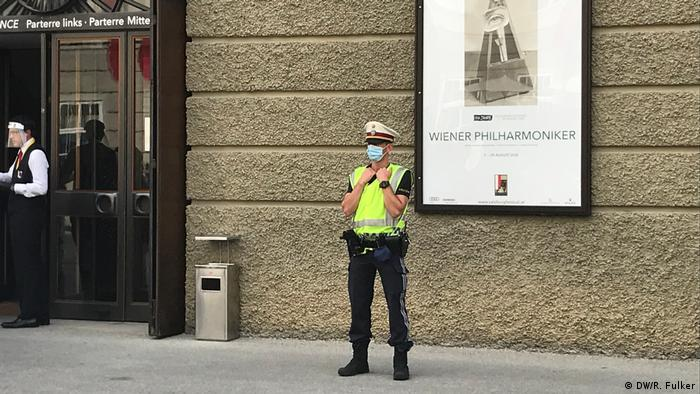 Masked police officer standing before a poster of the Vienna Philharmonic at the Festspielhaus