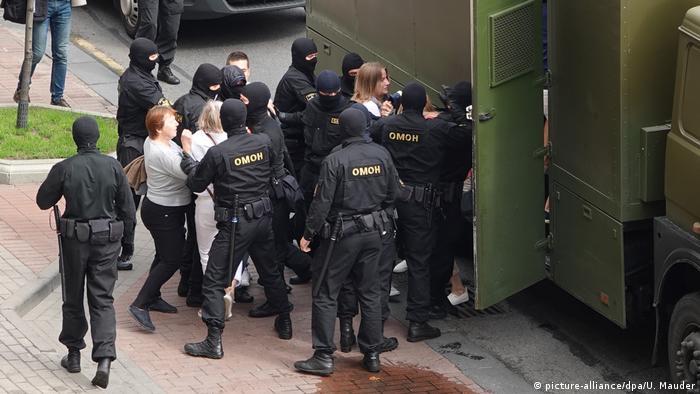 Сотрудники ОМОНа Беларуси в Минске ведут женщин в автозак